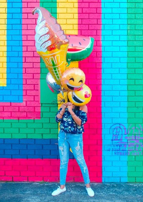 Nainen peittää kasvonsa värikkäillä foliopalloilla. Pallojen joukossa mm. naurava emoji, pehmis ja vesimeloni.