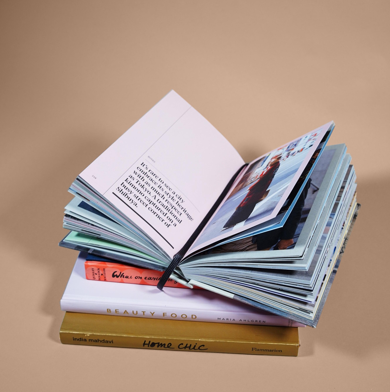 Pino kirjoja, joista päällimmäinen on avattuna keskeltä auki.