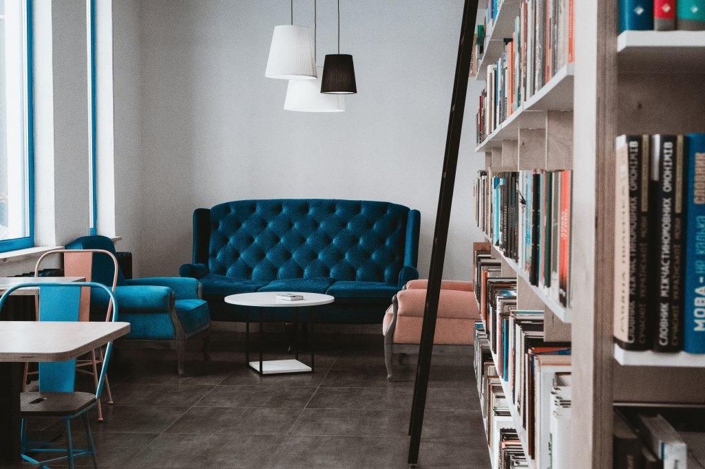 Turkoosi sohva kahvilassa. Seinustalla suuri kirjahylly.