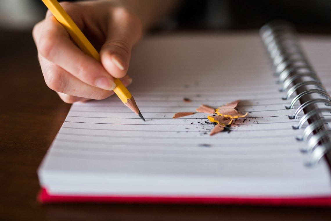 Käsi, jossa lyijykynä. Viivoitettu muistikirja, joka on vielä tyhjä. Muistikirjan päällä on teroitusroskaa